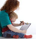 Writing on clipboard young woman and little girl Stock Image