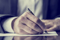 Writing correspondence man signing a document or with a close up view of his hand with the pen and sheet of notepaper on a desk Royalty Free Stock Images