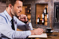 Writing down his ideas side view of handsome young man in shirt and tie something in note pad while sitting at the bar counter Royalty Free Stock Image