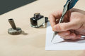 Writing with feather close up of man pen ink bottle Royalty Free Stock Images