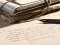 Writing a letter with a retro fountain pen concept lying on faded old and stack of vintage aged and worn correspondence Stock Image