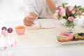 Writing in notepad woman ideas when sitting at table with different sweets Royalty Free Stock Image