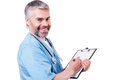 Writing rx prescription side view of mature doctor looking at camera and smiling while something at his clipboard and standing Royalty Free Stock Photo