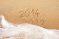Writing in the sand year ends and begins tide sea Stock Images