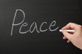 Writing the word peace hand on a used blackboard Stock Photo