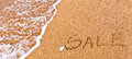 Written sale drawn on the sand Royalty Free Stock Photo