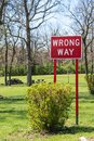 Red wrong way sign with bright green grass Royalty Free Stock Photo