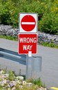 Wrong way sign posted on the road Royalty Free Stock Image