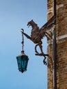 Wrought iron dragon with lantern decoration on brick wall Stock Image