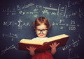 Wunderkind little girl schoolgirl with a book from the blackboar Royalty Free Stock Photo