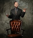 Wwell dressed man smoking cigar handsome well with glass of beverage and Royalty Free Stock Image