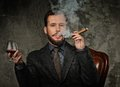 Wwell dressed man smoking cigar handsome well with glass of beverage and Stock Images