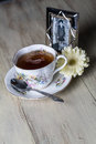 Xícara de chá antiga completamente do chá com a flor amarela da margarida e a fotografia velha Fotos de Stock Royalty Free