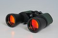 X binoculars with orange anti glare coated lenses against a grey background Stock Photography
