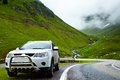 X car in the mountain landscape with a at side of road Royalty Free Stock Photo