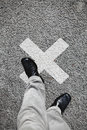 X marked the spot a feet stepping onto a on an asphalt road for concept of mark Stock Photography