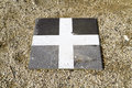 X marks the spot a single paving stone surrounded by gravel marked with a white cross Stock Photo