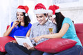 Xmas teenager drinking champagne group of with a tablet at home Stock Image