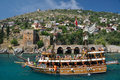 A yacht on the background of the fortress in alanya pleasure with tourists passes front june Royalty Free Stock Images