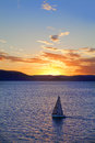 Yacht sailing on calm sea at sunset Stock Photos
