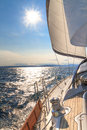 Yacht sailing towards sunset on blue sea Stock Images