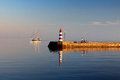 The yacht sails past the breakwater with a lighthouse Royalty Free Stock Photo