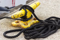 Yachting, black rope and yellow mooring bollard Royalty Free Stock Photo