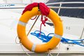 Yachting blue and red rope with orange lifebuoy on sailboat coiled deck of part of yacht safety travel Royalty Free Stock Images
