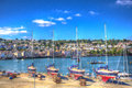 Yachts and a marina by a river with vivid blue sky and clouds in hdr like painting out of water Stock Photography