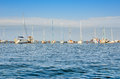 Yachts and sailing boats are on the dock. The small naval vessels are in the harbor on a background of blue sky Royalty Free Stock Photo