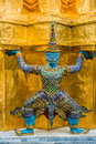 Yaksha demon grand palace bangkok thailand supporting golden chedi at Stock Photo