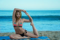 Yang woman practicing yoga by the ocean young pretty on beach Stock Photography