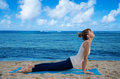 Yang woman practicing yoga by the ocean young pretty on beach Royalty Free Stock Images
