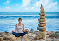 Yang woman practicing yoga by the ocean young pretty on beach Royalty Free Stock Photography