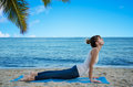 Yang woman practicing yoga by the ocean young pretty on beach Royalty Free Stock Photo