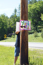 Yard sale a man nails a sign to a wooden post Royalty Free Stock Photo