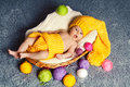 Yawning baby is lying in a basket. Around yarn for knitting. Royalty Free Stock Photo