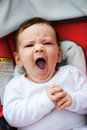Yawning baby sitting in stroller Stock Images