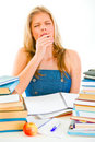 Yawning teen girl sitting at table with books Royalty Free Stock Photos