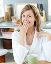 Yawning woman with a cup of coffee at home Stock Photography