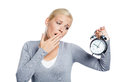 Yawning woman grey pullover alarm clock isolated white Royalty Free Stock Images