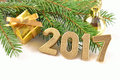Year golden figures on a spruce branch Stock Photos