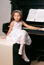 Year old girl black dress sitting near piano Stock Image