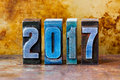 2017 year postcard. Colorful letterpress digits on rusty metal background. Retro style design xmas poster. Shallow depth