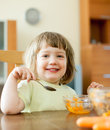 Years child eats carrot salad with spoon in home Stock Photos
