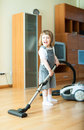 Years girl with vacuum cleaner on parque in living room Royalty Free Stock Photo