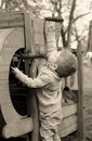 Years old curious baby boy managing with old agricultural mach machinery on sepia brown color Royalty Free Stock Image