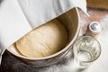 Yeast dough let stand to rise on old wooden table Stock Image
