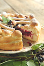 Yeast dough pie with black currant on wooden table Royalty Free Stock Photography