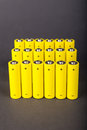Yellow alkaline batteries an array of batterieson grey background Stock Photos